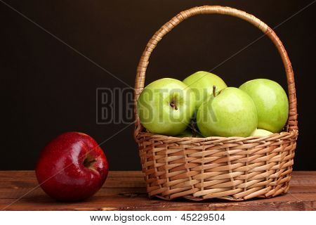 juicy green apples in basket and red apple on wooden table on brown background