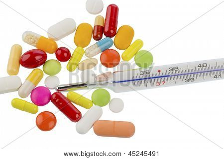 a thermometer and tablets. symbolic photo for flu and colds