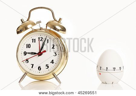 Alarm clock and kitchen timer over white background