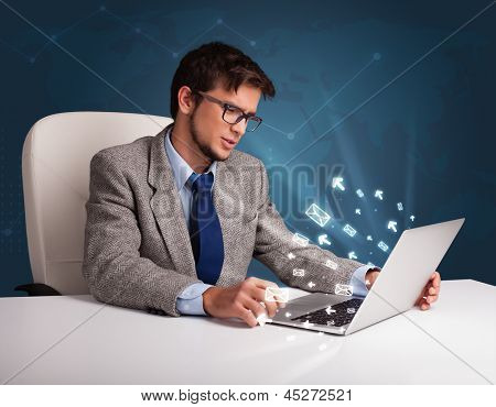 Attractive young man sitting at dest and typing on laptop with message icons comming out poster