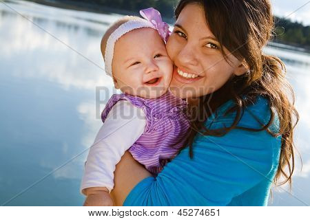 Mom And Baby Daughter Smiling By A Lake
