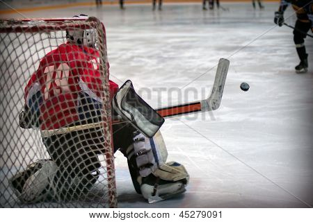 Hockey goalie in generic red equipment protects gate poster
