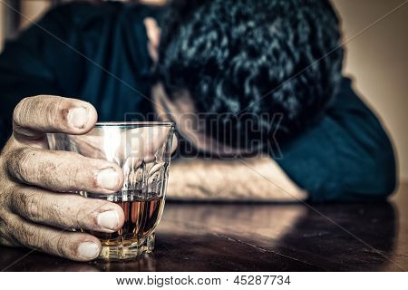 Depressed drunk man holding a drink and sleeping with his head on the table  (Focused on the drink, his face is out of focus)