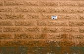 A bent sign glued to a painted moldy sandstone wall indicating that this is a parking space. poster