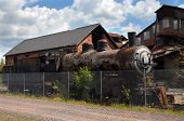 Old Northern Pacific Steam Locomotive sits inside the fence at the Quincy Copper Smelter in Hancock Michigan. Engine was used to transport copper during industry boom days. poster