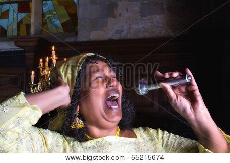 Closeup of a mature gospel or soul singer in a dark church
