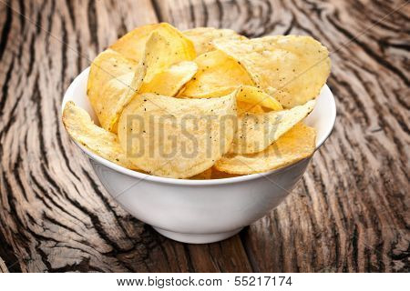 Potato chips in a bowl on a wooden table.