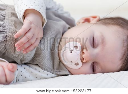 Cute baby girl sleeping over white bedcover
