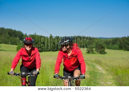 Sportive Man And Woman Riding Mountain Bike