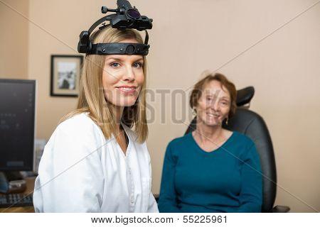 Portrait of confident female optometrist wearing binocular indirect ophthalmoscope