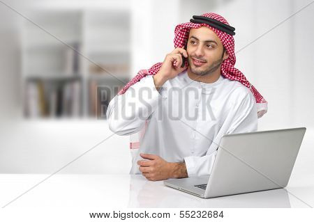 Arabian business man talking on phone in his office