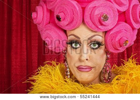 Doubting drag queen with wig frowning in theater poster