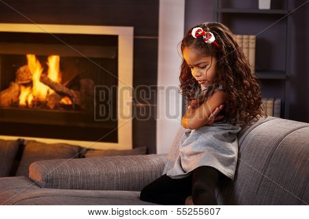 Sulky little afro girl in living room by fireplace.