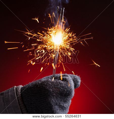 sparkler in hand mitten, close-up view, red background poster