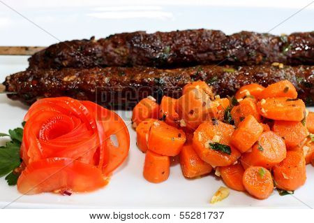 Closeup scene of grilled meat with carrots saute