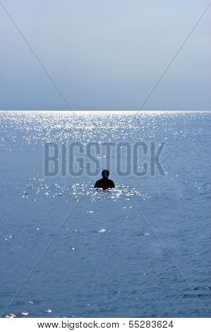 Silhouette of a Man Swimming on a Beach