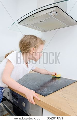 Little Girl Wipes Cooktop In The Kitchen At Home.