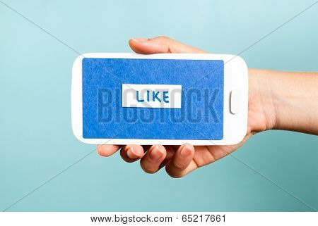 Hand holding phone concept showing like button on blue background