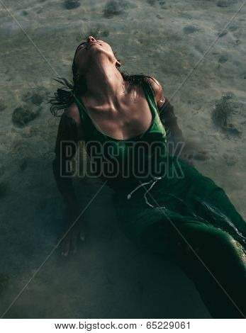 Sensual portrait of a young woman bathing in the sea wearing a green dress clinging to her shapely body as she reclines in the shallow water with her head tilted back