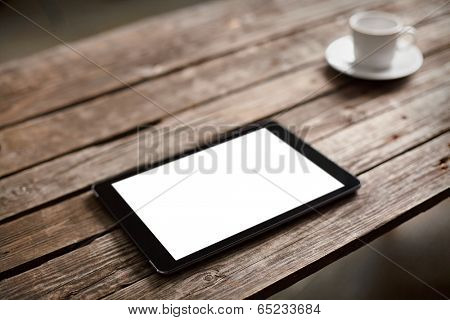 Digital tablet computer with isolated screen on wooden table with cup of coffee