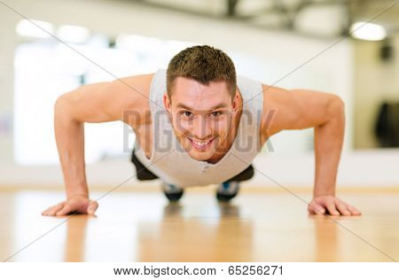 fitness, sport, training, gym and lifestyle concept - smiling man doing push-ups in the gym poster