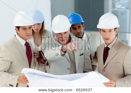 Serious Architect Looking At Blueprints And Pointing