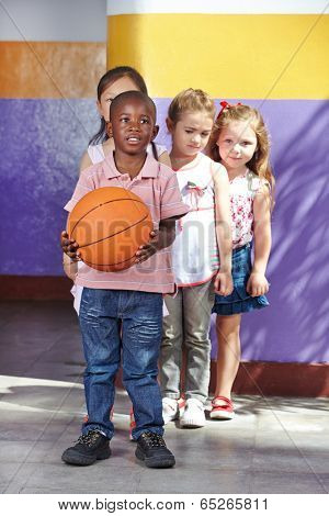Children playing with basketball in a kindergarten