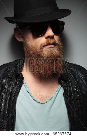 close up portrait of a casual young man with a long beard, sunglasses and a trilby hat, looking away . on a dark studio background