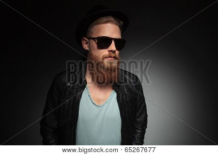 casual young man with a long red beard and a trilby on his head, looking away from the camera. on a dark studio background