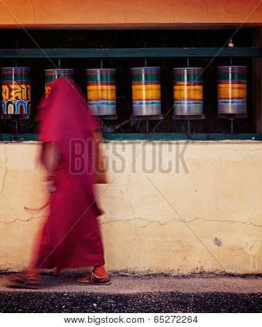 Vintage retro effect filtered hipster style travel image of Buddhist monk with prayer beads passing spinning prayer wheels on kora around Tsuglagkhang complex in McLeod Ganj, Himachal Pradesh, India