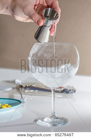Barman pouring drink to prepare gin tonic cocktail