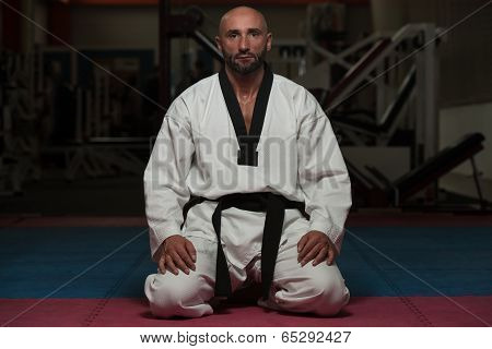 Black Belt Karate Man Sit On A Position To Start Or Finish Practicing poster