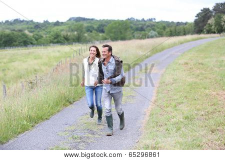 Cheerful couple of farmers running in countryside