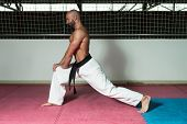 Male Martial Arts Instructor Preparing For Class - Warming Up and Stretching poster
