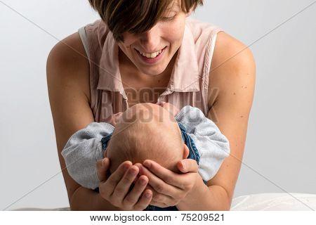 Smiling Mother Cradling Her Newborn Baby
