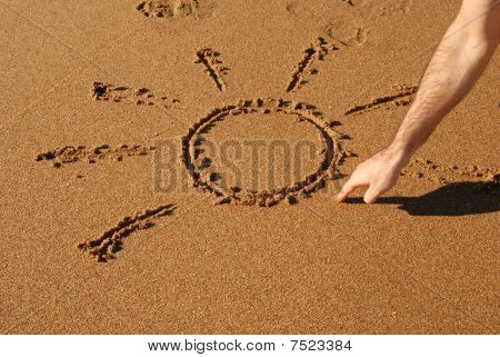 Hand Drawing A Sun In The Sand