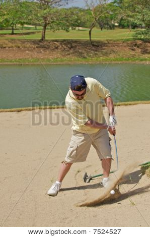 Man hitting a golf ball out of a sand trap