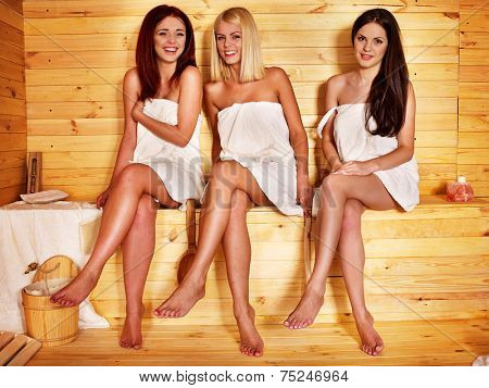 Group people relaxing in sauna.