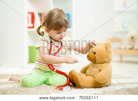 child girl playing doctor and curing plush toy