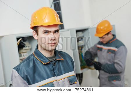 two electrician builder engineer workers in front of fuse switch box