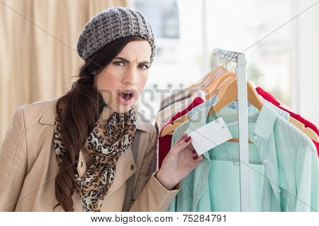 Pretty brunette shocked at price of shirt at clothes store