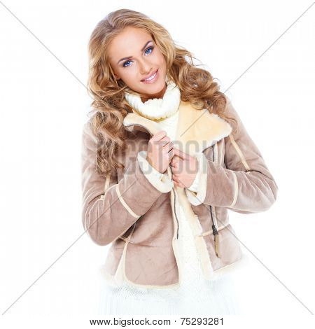 Stylish young woman in winter fashion wearing a lovely thick warm jacket and polo neck smiling happily at the camera  on white