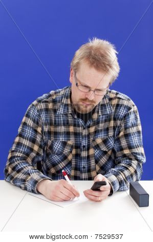 Man writes notes at his office desk