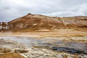 Geothermal region of Hverir in Iceland near Myvatn Lake with fumaroles venting pressurised gases sulphur springs and hot boiling mud from volcanic activity poster