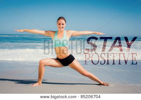 Fit woman standing on the beach in warrior pose against stay postive