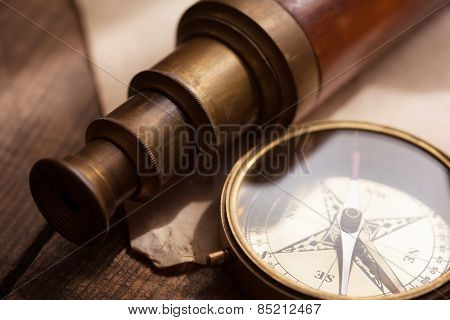 Vintage telescope and compass, on an grungy wood table. Focus is on compass glass and telescope third extension section rim. Shallow depth of field. Intentionally shot with low key shadows.