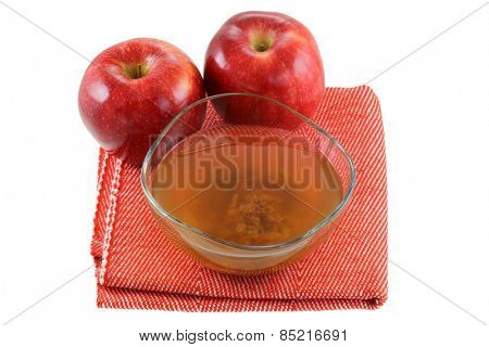 Fresh apples and a bowl of raw and unfiltered organic apple cider vinegar with mother enzymes isolated on white
