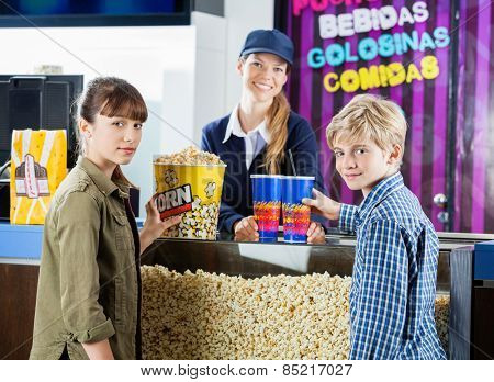 Portrait of brother and sister buying snacks from female seller at cinema concession stand