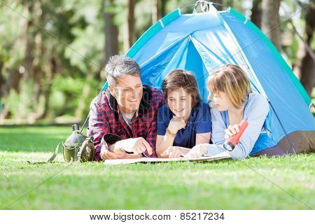 Happy family studying map while lying in tent at park