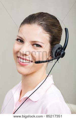 Portrait of happy female call center employee with headphones at office